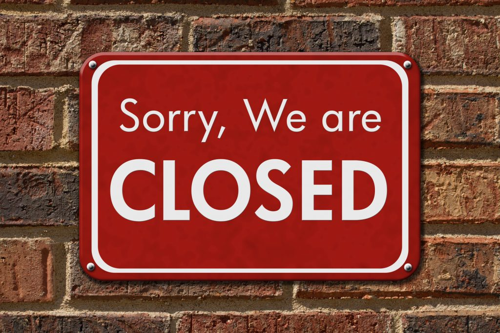 Sorry We are Closed Sign, A red hanging sign with text Sorry We are Closed on a brick wall