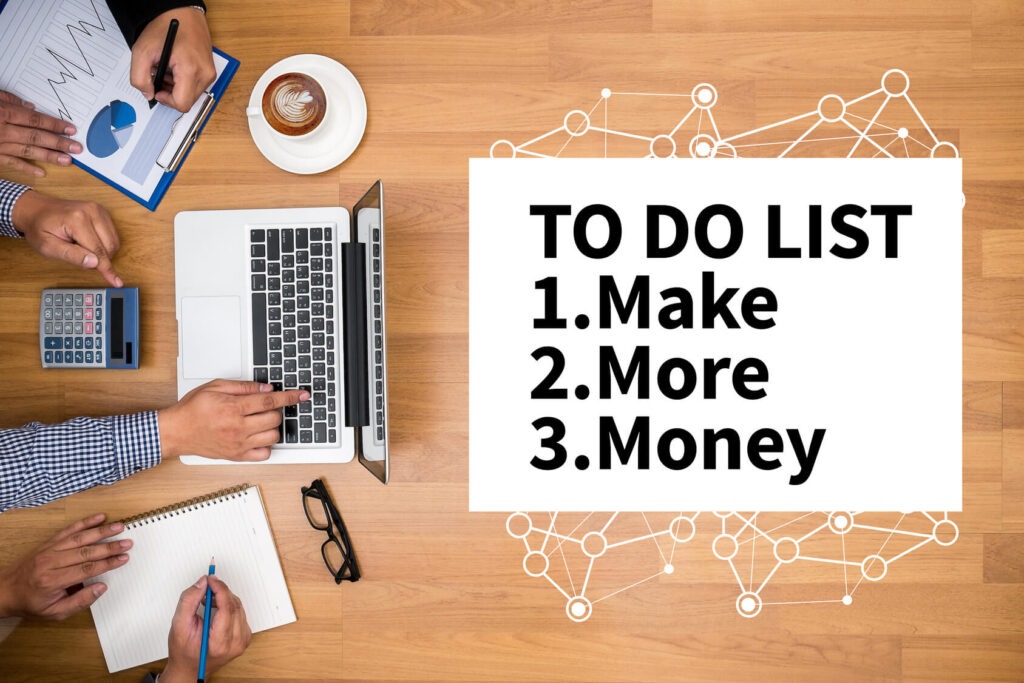 TO DO LIST - Make More Money Business team hands at work with financial reports and a laptop